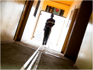 Picture of a man silhouetted in a doorway. He is walking down a hallway on 3 continuous ceramic strips. He is using a mobility cane.
