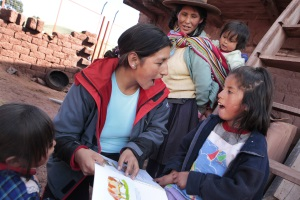 Picture of a girl from Peru sitting on a ladder outside of her house.  She is reading a book with the CBR worker. Her mother and baby sister are watching.