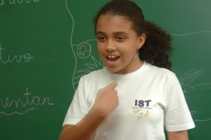 Picture of a girl from Brazil standing in front of a blackboard using sign language.