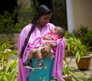Picture of a mother from India holding her baby girl who has clubfeet. The baby has Ponseti boots on both of her feet.