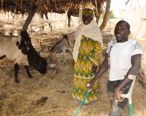 Picture of a man in Niger, who uses crutches, and a woman, standing next to a goat and a donkey. The animals are under a thatched roof shelter.