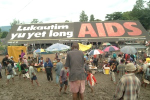 "Picture of a billboard at a busy market in PNG that reads ""Lukautim yu yet long AIDS"""