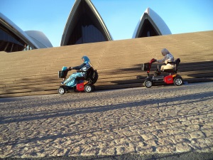 Picture of two women from using motorised scooters driving past the Sydney opera house.