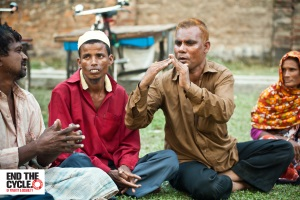 Picture of Waddud (third from left) two men and an older woman sitting on the grass outside using sign language to communicate.