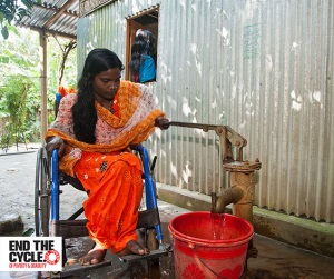 Picture of a woman in Bangladesh who is a wheelchair user at an accessible water pump. The water pump is low enough to be reached sitting down, and has a long handle which she is using to collect water in a plastic bucket underneath.