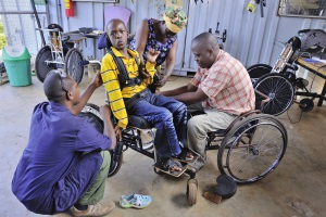 Picture of a teenage boy from Tanzania sitting in his wheelchair whilst it is being adjusted. There are two technicians carrying out the repairs, one of the technicians is also a wheelchair user. His mother is watching the process from behind.