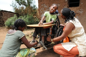 Picture of a girl from Tanzania who is sitting in a wheelchair fitted with a tray table outside a building.  She is smiling at the female CBR worker who is squatting beside her to her right. Her mother is squatting down in front of her adjusting a strap holding the child's right foot in place on the wheelchair foot support.