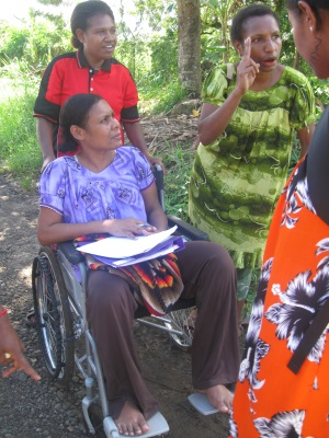 Picture of three women from Papua New Guinea collecting information about road use. One of the women is using a wheelchair and has data sheets on her lap.