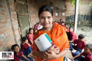 Ruma stands confidently holding a text book with Bangla characters. She is wearing a beautiful orange beaded and embroidered shawl and dress. Behind her, a group of around 10 young Bangladeshi boys and girls in school uniforms sit on the ground outside, next to a brick building, ready for a lesson, together with some young women and young children.