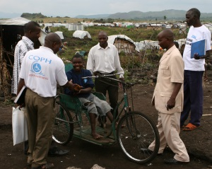 Picture of a group of field workers meeting a man who has a mobility impairment from the Democratic Republic of Congo. The man is using a hand propelled tricycle. There are many tents in the background.