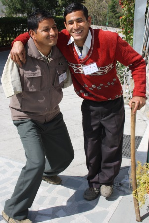 Picture of two smiling young men. One, who uses a walking stick , has his arm around his friend. His friend has no arms.