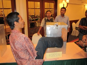A man from Indonesia who has no arms, uses his foot to place a ballot paper in the locked metal ballot box. The ballot box is high on a table. Three men are watching from the other side of the table.
