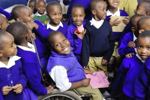 Picture of a young boy from Tanzania who uses a wheelchair. He is smiling and is surrounded by his classmates who are crowding around him.