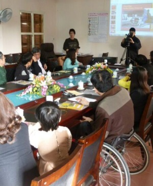 A number of men and women from Vietnam, including a wheelchair user (third from the left) sit around a table participating in discussion, and watching a powerpoint presentation.