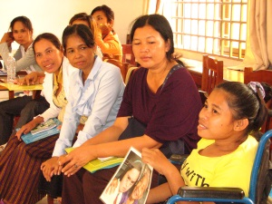 Picture of a group of 7 women from Cambodia sitting in a meeting room.  The woman to the front of the picture is a wheelchair user. She is holding a picture and speaking. The other women are all listening to her.